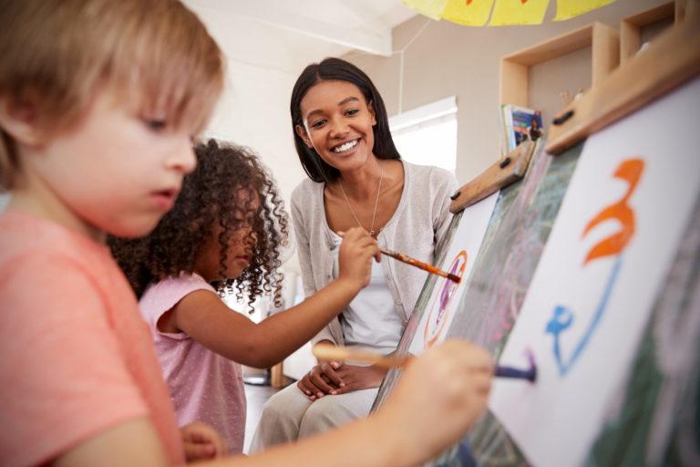 Profesora de Montessori pintando con sus alumnos