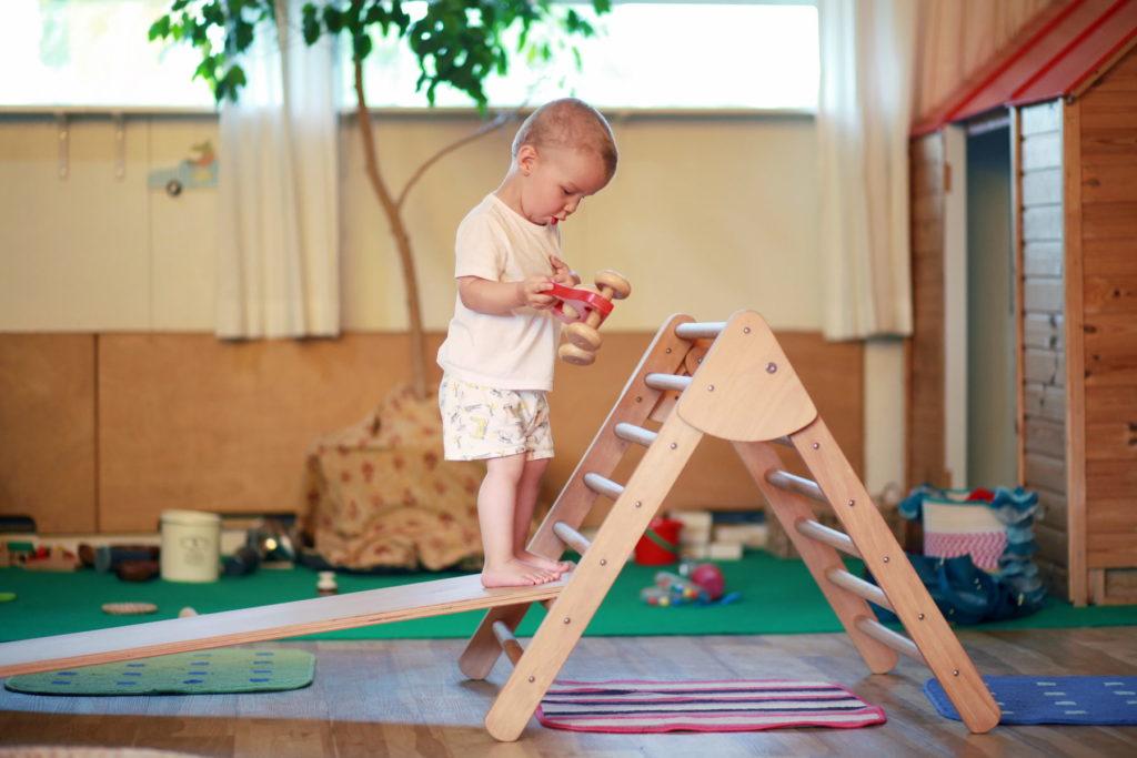 Niño en escuela Montessori jugando con elemento Pikler